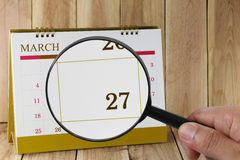 Magnifying glass in hand on calendar you can look Twenty seven d. Ay of month,Focus number Twenty seven in March,Concept in business and meetings Stock Images