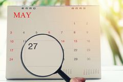 Magnifying glass in hand on calendar you can look Twenty seven d. Ay of month,Focus number Twenty seven in May,Concept in business and meetings Stock Images