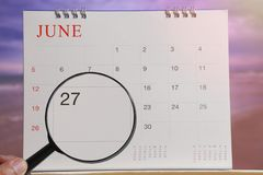 Magnifying glass in hand on calendar you can look Twenty seven d. Ay of month,Focus number Twenty seven in June,Concept in business and meetings Stock Photography