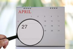 Magnifying glass in hand on calendar you can look Twenty seven d. Ay of month,Focus number Twenty seven in April,Concept in business and meetings Stock Photos