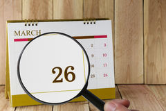 Magnifying glass in hand on calendar you can look Twenty-six day Royalty Free Stock Images