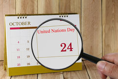 Magnifying glass in hand on calendar you can look United Nations Royalty Free Stock Photo