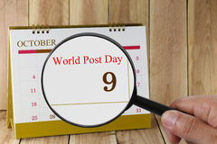 Magnifying glass in hand on calendar you can look World Post Day. In 09 October,concept of a public relations campaign Stock Photography