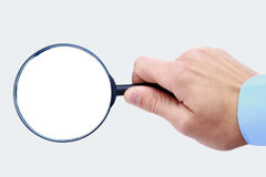 Magnifying glass in hand Stock Images