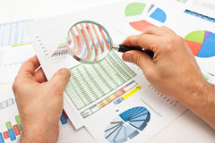 Magnifying glass in hand and paper Stock Images