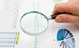 Magnifying glass in hand and paper Stock Image