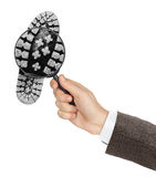 Magnifying glass in hand and shoe printout Royalty Free Stock Image
