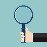 Magnifying glass in a hand Royalty Free Stock Images
