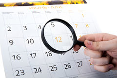 Magnifying glass in hand and the wall calendar Stock Photo