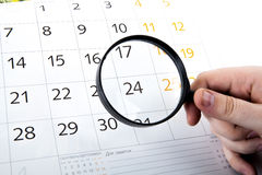 Magnifying glass in hand and the wall calendar Royalty Free Stock Photo
