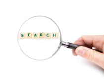 Magnifying glass in hand on the word search. Stock Photos