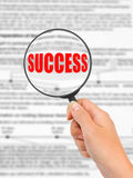 Magnifying glass in hand and word Success Royalty Free Stock Photography