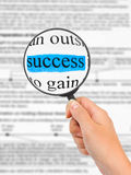 Magnifying glass in hand and word Success Stock Image