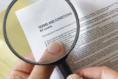 Magnifying glass. Hands holding magnifying glass reading terms and conditions of loan agreement stock photography