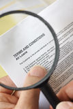 Magnifying glass. Hands holding magnifying glass reading terms and conditions of loan agreement royalty free stock image