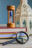 Magnifying glass and hourglass Royalty Free Stock Photos