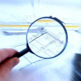 Magnifying glass and house plan. Magnifying glass searching the measurements of a house plan Stock Photo