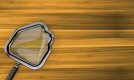 Magnifying glass in house shape. On wooden background Royalty Free Stock Photo