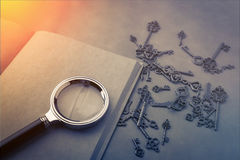 Magnifying glass and a key on blank page notebook Royalty Free Stock Photo
