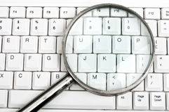 Magnifying glass on keyboard Royalty Free Stock Image
