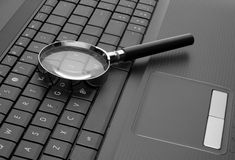 Magnifying glass on laptop Stock Image