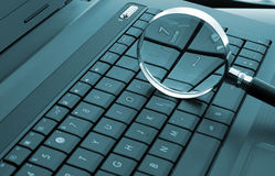 Magnifying glass on laptop Stock Photography