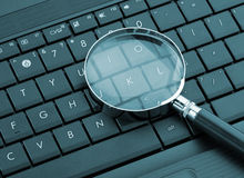 Magnifying glass on laptop Royalty Free Stock Photography