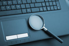 Magnifying glass on laptop Royalty Free Stock Images