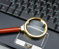 Magnifying glass and a laptop Stock Photos