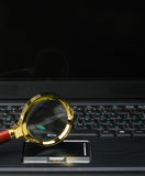 Magnifying glass and a laptop Royalty Free Stock Image