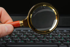 Magnifying glass and a laptop Royalty Free Stock Photo