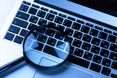 Magnifying glass on laptop Royalty Free Stock Image