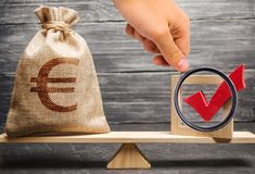 Magnifying glass is looking at a bag with euro money and a red check mark of a voice on scales. Intervention in the political. Processes. lobbying for laws and royalty free stock photo