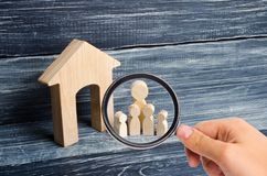 Magnifying glass is looking at the Big family is standing near the house. Wooden figures of persons stand near a wooden house. The concept of a couple in love royalty free stock photography