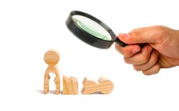 Magnifying glass is looking at a broken wooden human figure and a mother with a void in the body. Strife in the family. One parent. Is broken, addicted to drugs royalty free stock photos