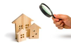 Magnifying glass is looking at the City of wooden houses on a white background. The concept of urban planning, infrastructure proj royalty free stock photo