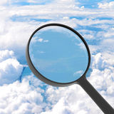 Magnifying glass looking clouds in background Royalty Free Stock Image