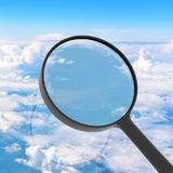 Magnifying glass looking clouds in background Stock Photo