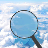 Magnifying glass looking clouds in background Stock Photos