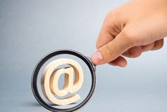 Magnifying glass is looking at the Email icon on gray background. internet correspondence, communication on the Internet. Contacts. For business. Establishing stock image