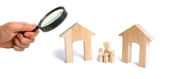 Magnifying glass is looking at the family with children stand between two houses. the designation of the future family. Make a decision, they make a choice royalty free stock images