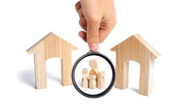 Magnifying glass is looking at the family with children stand between two houses and make a decision, they make a choice. The designation of the future family royalty free stock images