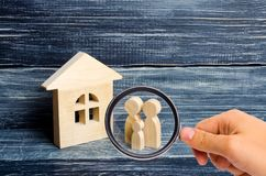 Magnifying glass is looking at the Family is standing near the house. Wooden figures of persons stand near a wooden house. The concept of a couple in love stock photos