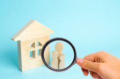 Magnifying glass is looking at the Family is standing near the house. Wooden figures of persons stand near a wooden house. The concept of a couple in love royalty free stock image