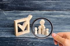 Magnifying glass is looking at the Family wooden human figures stand together next to a tick in the box. elections. And social technologies. Volunteers, parties royalty free stock images