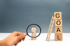 Magnifying glass is looking at the figure of a man stands near a tower of cubes with the word goal. achieving the goal, dedication stock images