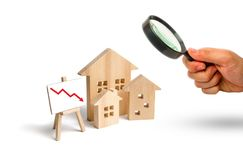 Magnifying glass is looking at the figures Wooden houses and red arrow down. The concept of falling prices and demand for real. Estate, crisis and recession royalty free stock photo