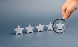 Magnifying glass is looking at five stars on a gray background. The concept of rating and evaluation. The rating of the hotel royalty free stock photo