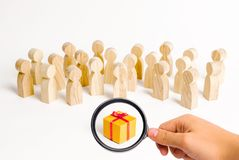 Magnifying glass is looking at the large group of people looking at a gift. choosing a good gift, a limited number, all sold out. stock image