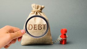 A magnifying glass is looking at a money bag with the word Debt and a borrower is bound by handcuffs. Mandatory payment of debt. royalty free stock photo